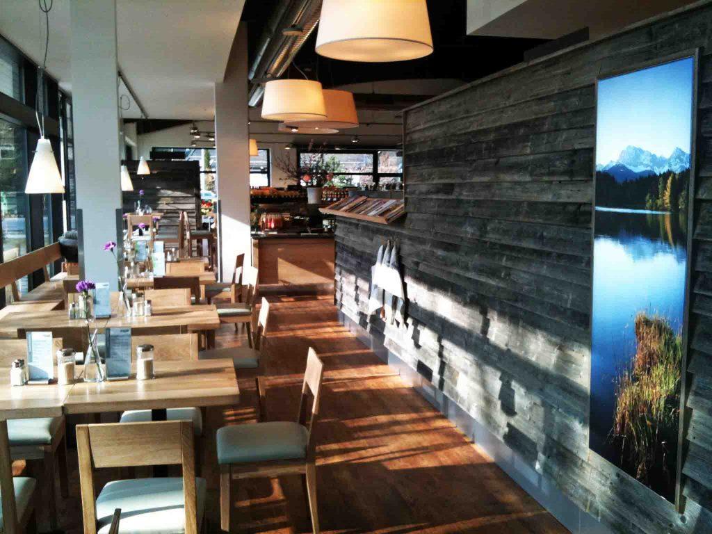 Blick auf den Restaurant-Bereich des Alpenbiomarktes, wo mehrere Tische an den großen Fenstern stehen.