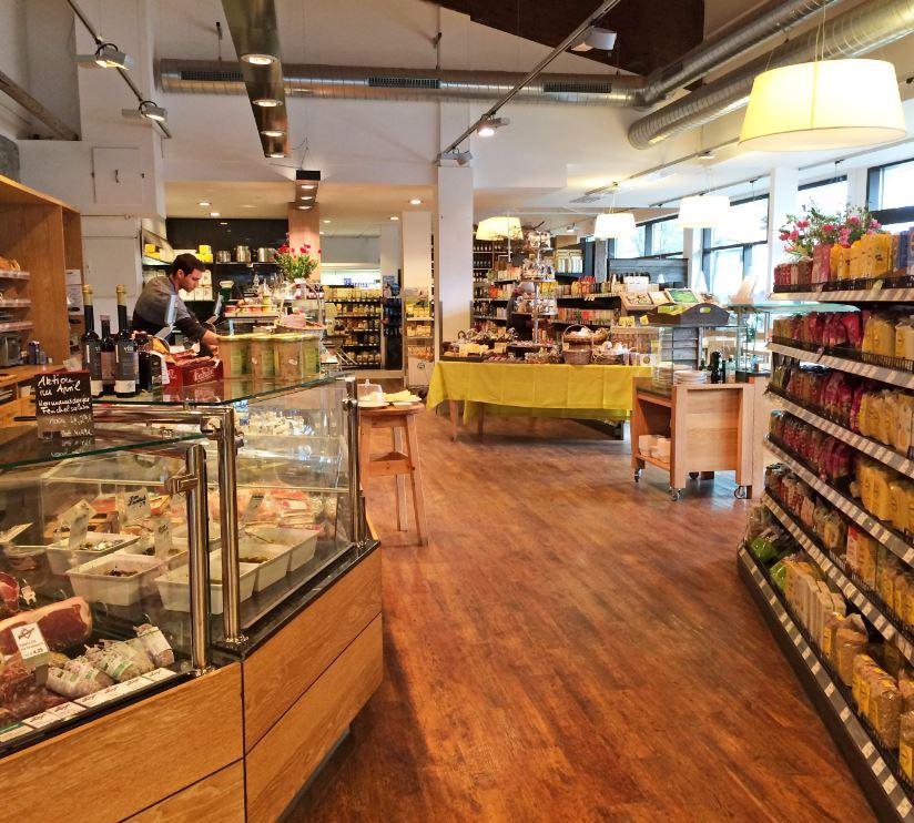 Das Bild zeigt den weitläufigen Verkaufsraum des Alpenbiomarktes mit den Bedientheken mit Fleisch und Antipasti.