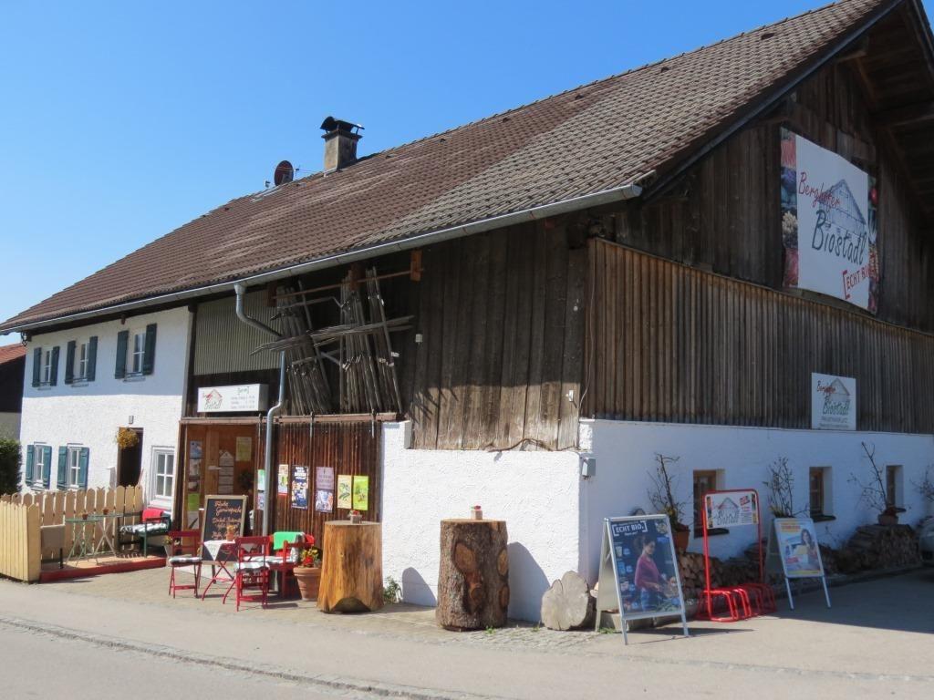 Außenansicht des Hauses mit dem Berghofer Biostadl. Man sieht den Eingangsbereich mit Tischen und Plakaten davor.