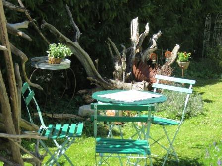 Man sieht einen Gartentisch mit Stühlen im Freien vor einer Hecke. Die Sonne scheint.