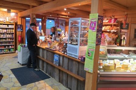 Innenansicht des Ladens. Man sieht den Kassenbereich hinter einer Holztheke, die Käsetheke und einen Kunden mit Verkäuferin an der Kasse.
