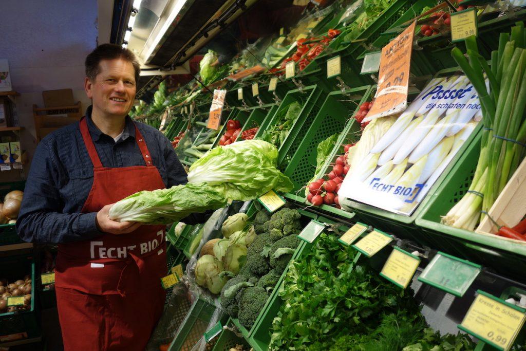 Hier sieht man einen Ladner, der vorm Obst- und Gemüseregal Produkte hält.