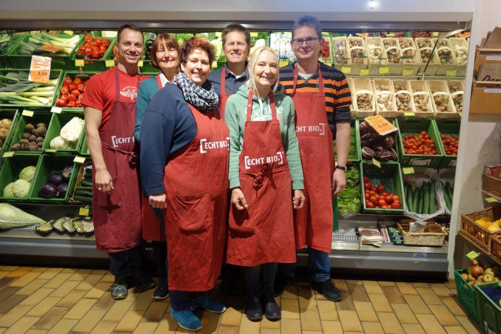 Gruppenfoto des Teams des BioMartk Tutzing. Sie stehen in roten ECHT BIO-Schürzen vorm Obst- und Gemüseregal.