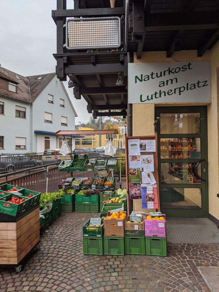 Das Bild zeigt den Außen- und Eingangsbereich des Naturkost am Lutherplatz. Im Außenbereicht stehen Kisten mit verschiedenen Obst- und Gemüsesorten zum Angebot.