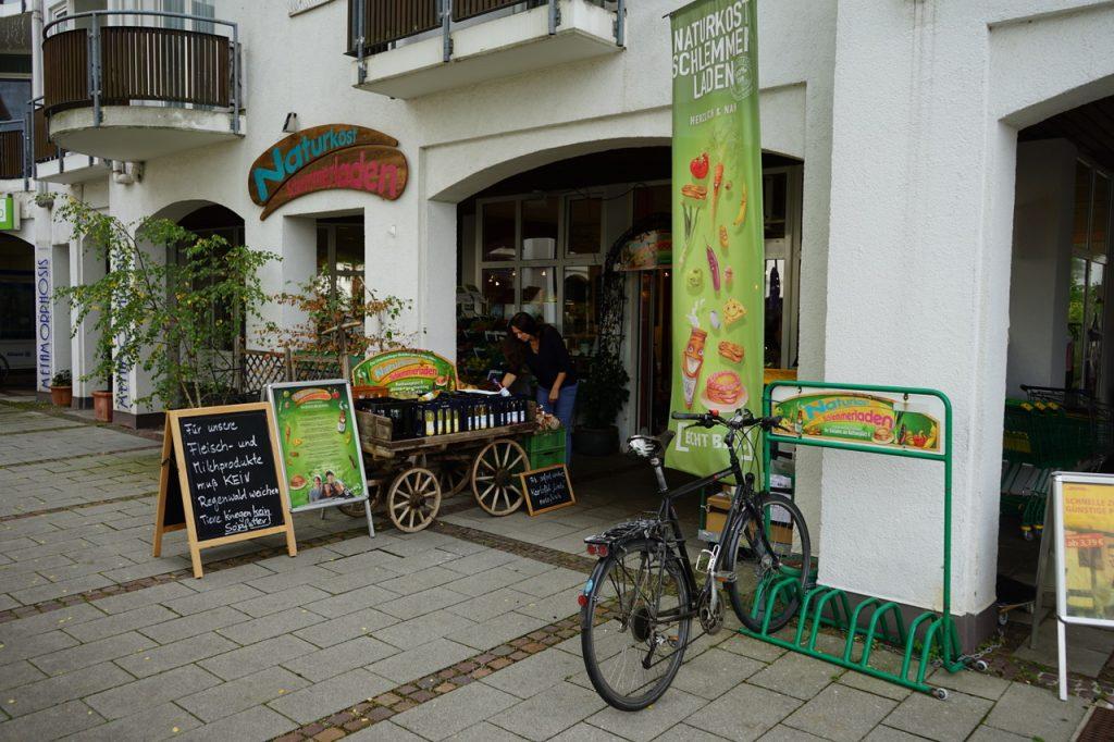 Blick auf den Eingangsbereich des Schlenmmerladens. Es gibt einen Fahrradständer und Schilder mit Angeboten.