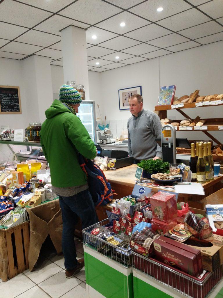 Kundeneinkauf an der Kasse. Im Hintergrund sieht man das Regal mit frischem Brot und links und rechts Angebote mit Weihnachtsware.