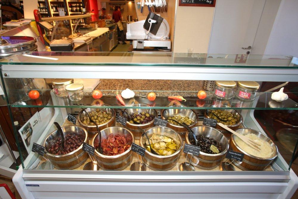 Die Antipasti Theke sieht schmackhaft aus. Es gibt diverse Oliven und eingelegtes Gemüse.