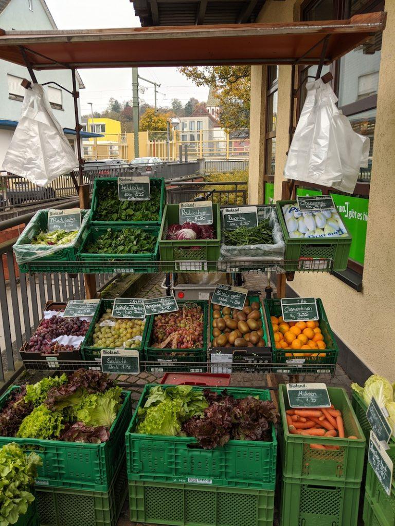 Man sieht frische Salate, Gemüse und Obst in der Auslage im Freien.