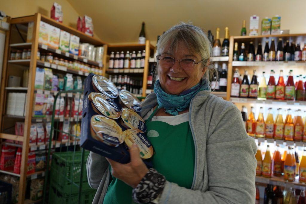 Eine breit lächelnde Mitarbeiterin hält einige Grießpuddings hoch. Im Hintergrund sieht man Regale mit Wein und Getränken.