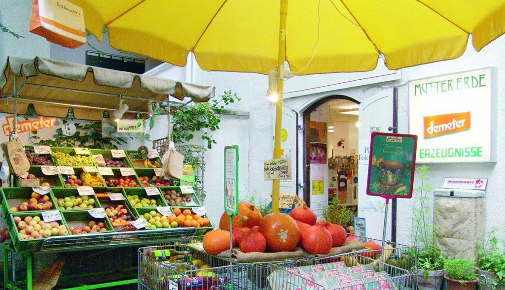 Außenbereich der Mutter Erde. Unter einem gelben Sonnenschirm sieht man Kürbisse und im Hintergrund eine Auslage von Obst und Gemüse sowie daneben den Eingang zum Laden.