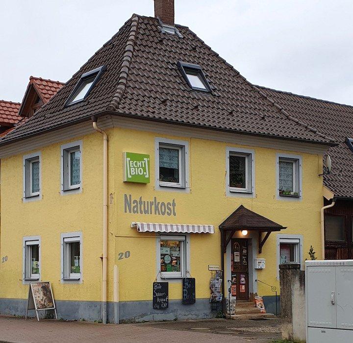 Außenansicht auf das gelbe Haus, in dem sich Naturkost Schäfer befindet.