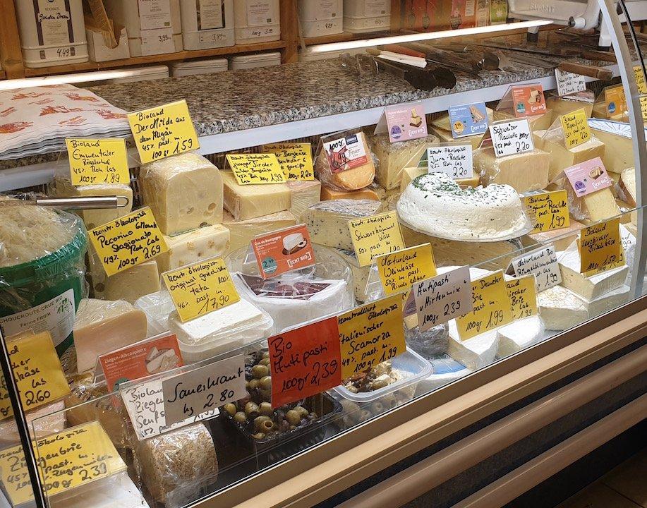 Käsetheke mit verschiedenen Käse- und Frischkäsesorten sowie Oliven.