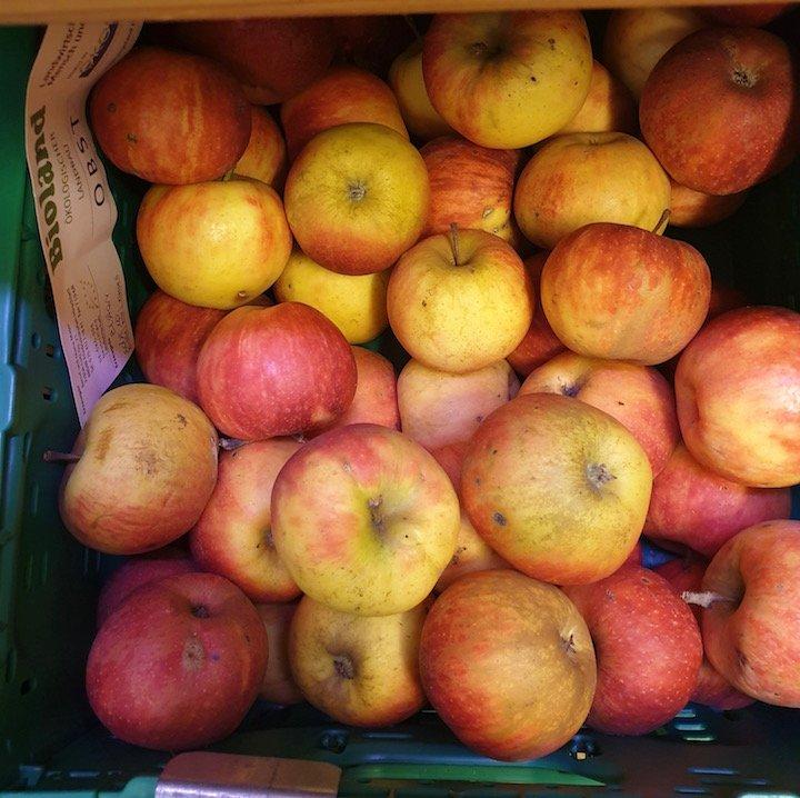 Frische Bioland-Äpfel in einer grünen Kiste.