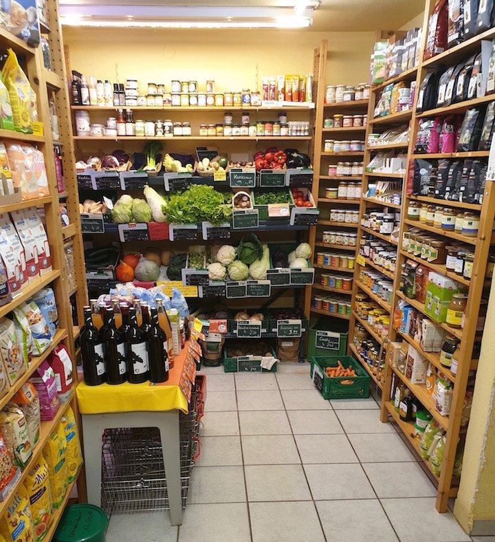 Blick in den Laden auf mehrere Regale mit Tee, Honig, Müsli, Aufstrichen und Gemüse.