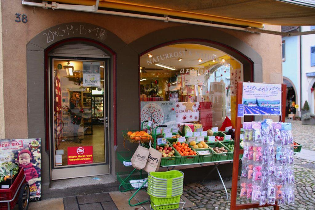 Frontansicht des aradia Naturkost und Naturkosmetik. Man sieht einen Auftseller mit Obst und Gemüse vorm Schaufenster.