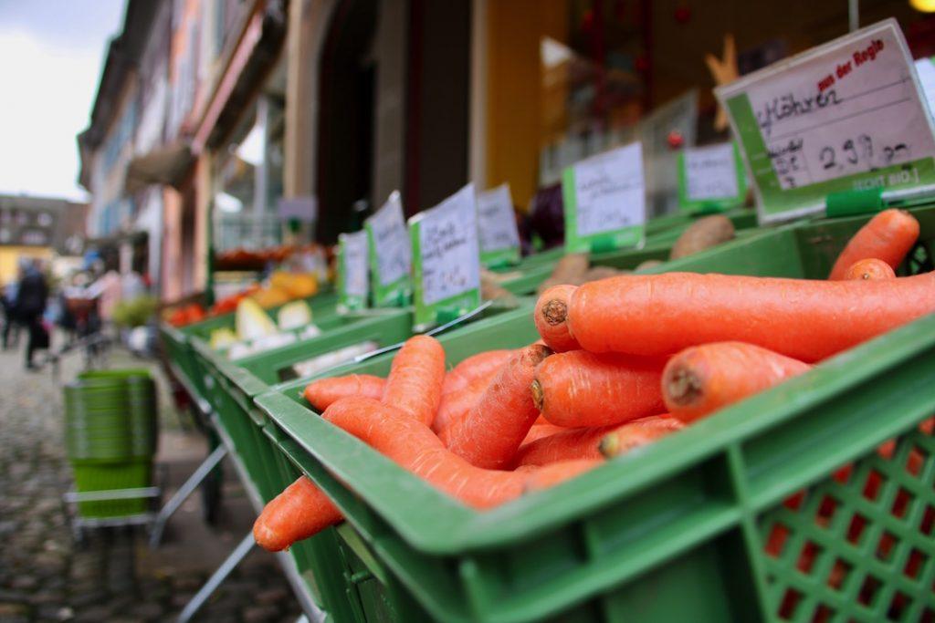 Eine Gemüsekiste mit schön orangen Karotten vorm aradia Naturkost und Naturkosmetik.