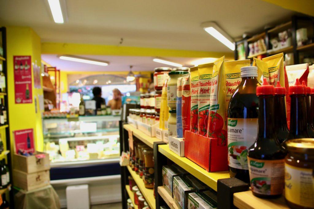 Foto von einem Produktregal und der Käsetheke im aradia. Im Hintergrund sind zwei Personen zu sehen.