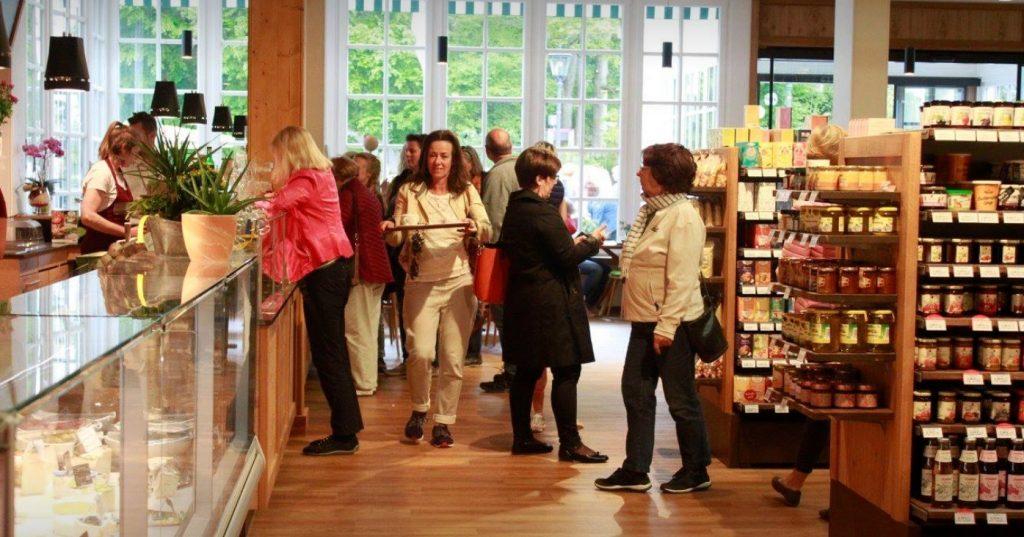 Zu sehen sind mehrere Kundinnen und Kunden im breiten Gang zwischen Regalen mit Produkten und Bedientheke mit Käse.