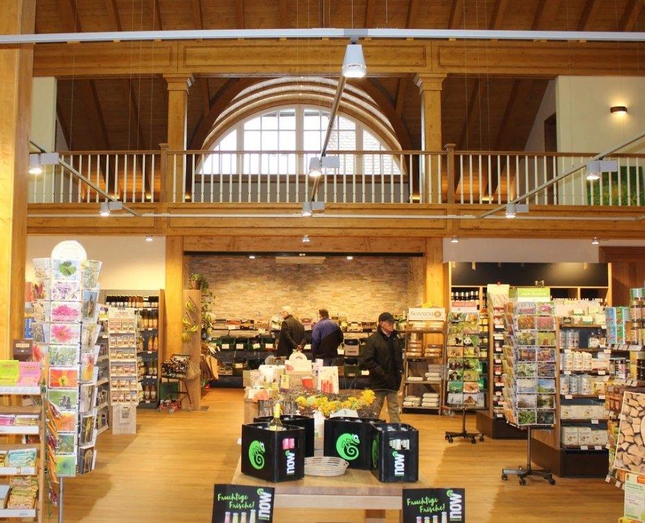 """Innenansicht der Bio Oase. Man sieht die hohen Decken und den großen Verkaufsraum, in dem Postkarten, Weine, Obst und Gemüse und Limonade der Marke """"NOW"""" zu zu sehen sind."""