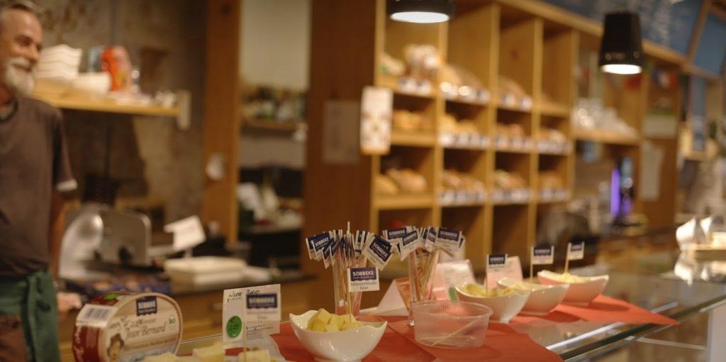 Das Bild zeigt eine Verkostung mit Käse der Marke Söbbeke an der Theke. Hinter der Bedientheke steht ein lächelnder Ladner und im Hintergrund sind Brote zu sehen.