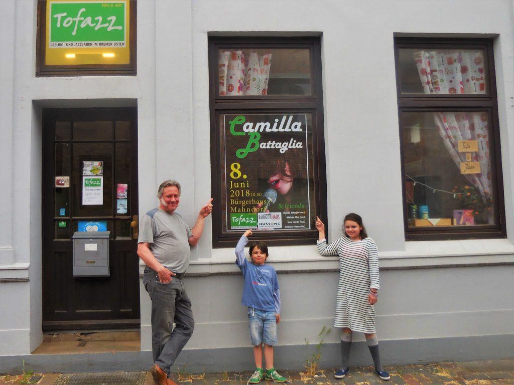 Man sieht die Familie vor einem Schaufenester mit einem Plakat für einen musikalischen Auftritt im Tofazz.
