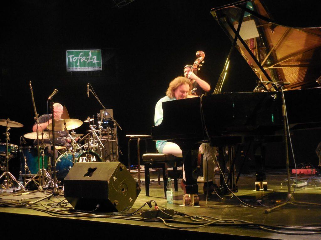 Das Bild zeigt einen Bühnenauftritt mit Flügel, Schlagzeug und Kontrabass im Tofazz.