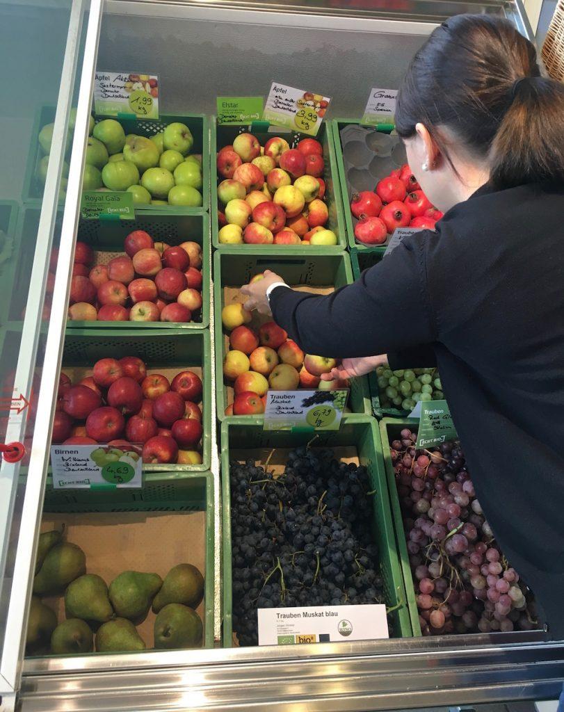 Man sieht die Obst- und Gemüseauslage und eine Frau von hinten, die Äpfel aus der Kiste nimmt.