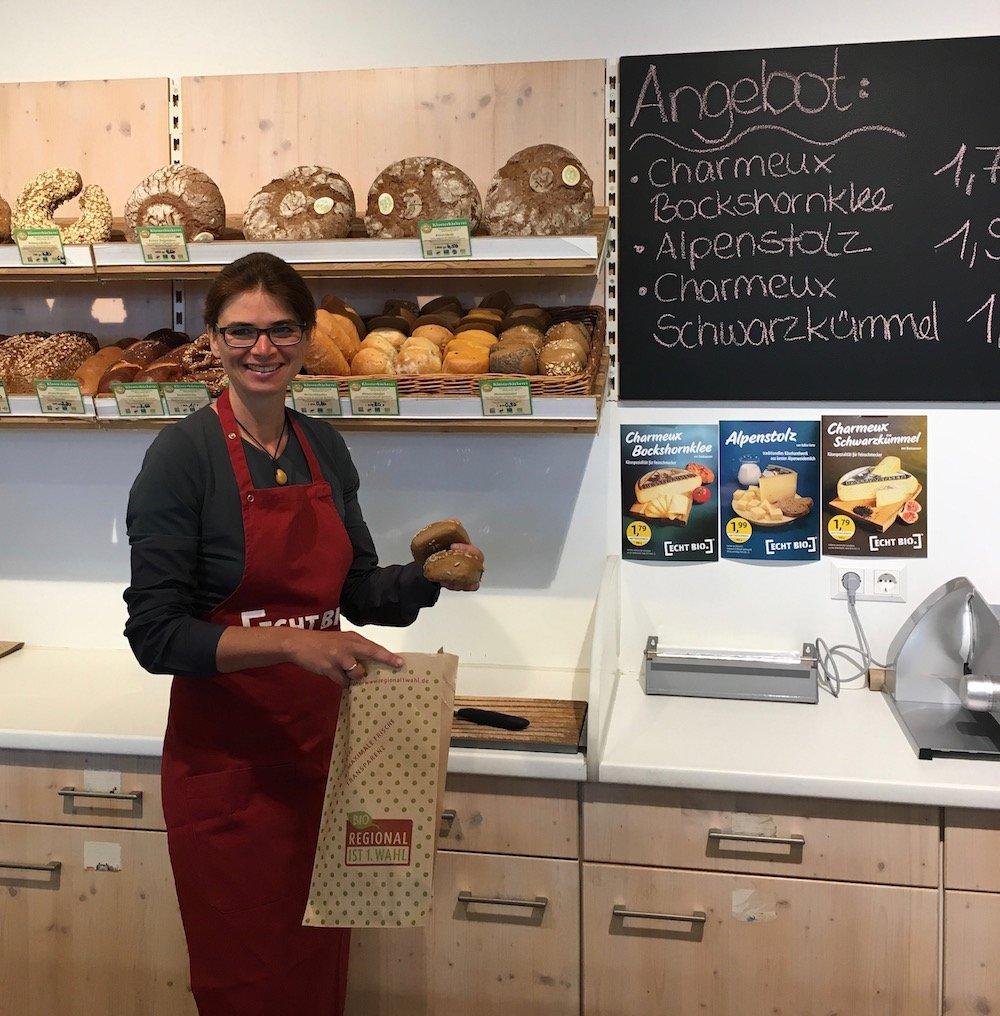 Eine lächelnde Verkäuferin verpackt Brötchen in einer regional ist 1. Wahl Tüte. Außerdem sieht man eine Tafel, auf der das ECHT BIO-Käseangebot zu lesen ist.