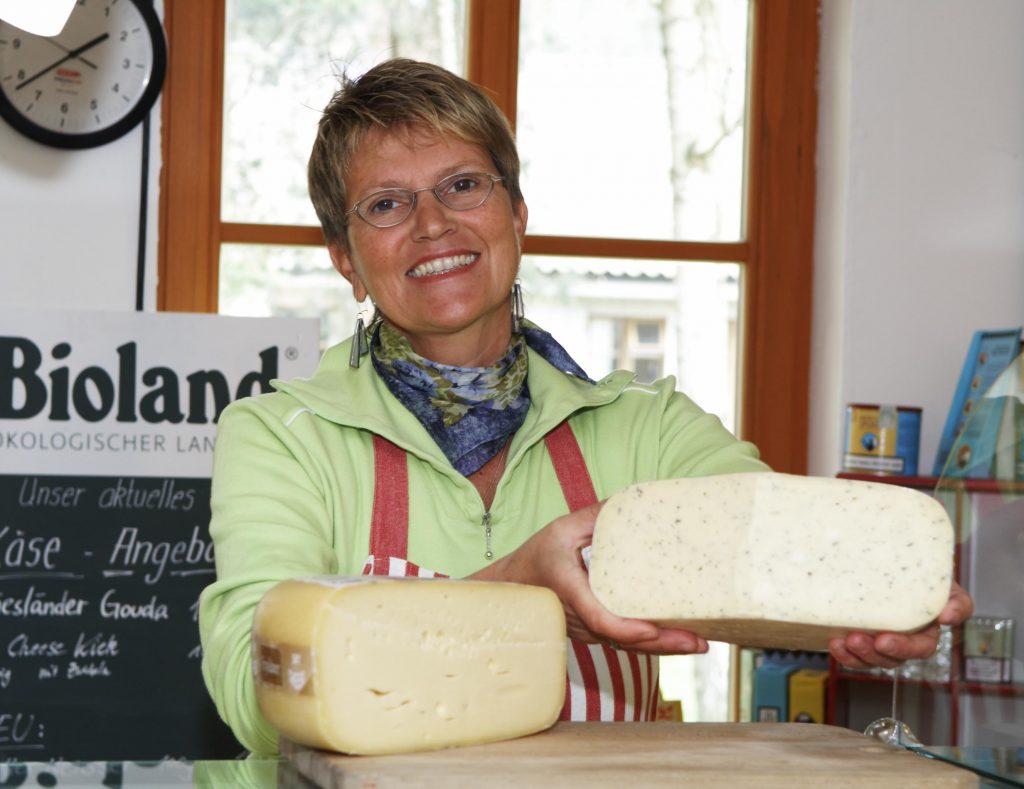 Man sieht eine lächelnde Landerin, die der Kamera ein angeschnittenes Laib Käse entgegenhält. Im Hintergrund steht der Schriftzug Bioland.