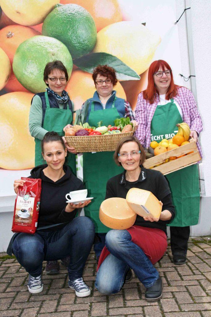 Das Naturalia-Team mit Produkten - von Frische über Käse bis zu Kaffee.