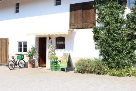 Außenansicht auf die weiße Fassade des Hofladens mit duklen Fensterläden aus Holz.