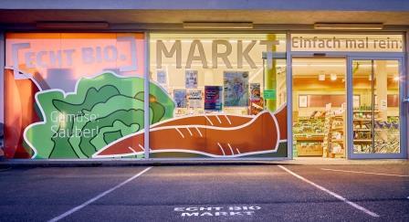 Blick auf den Eingang des ECHT BIO Markt Riedlingen. Man sieht die Schaufenstergestaltung, die Karotten und Salat abbildet.