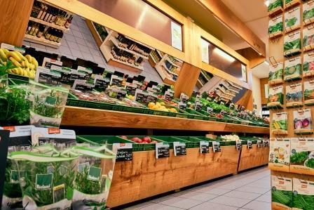 Innenansicht auf das Obst- und Gemüseangebot. Im Spiegel darüber sieht man Ausschnitte von Regalen mit weiteren Produktgruppen.