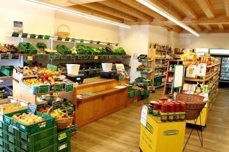 Innenansicht des Ladens. Man sieht links üppige Obst- und Gemüseregale.
