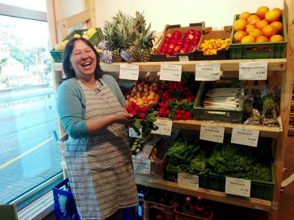 Ladnerin mit freundlichem Lachen, die vor dem Gemüseregal frische Radischen hält.