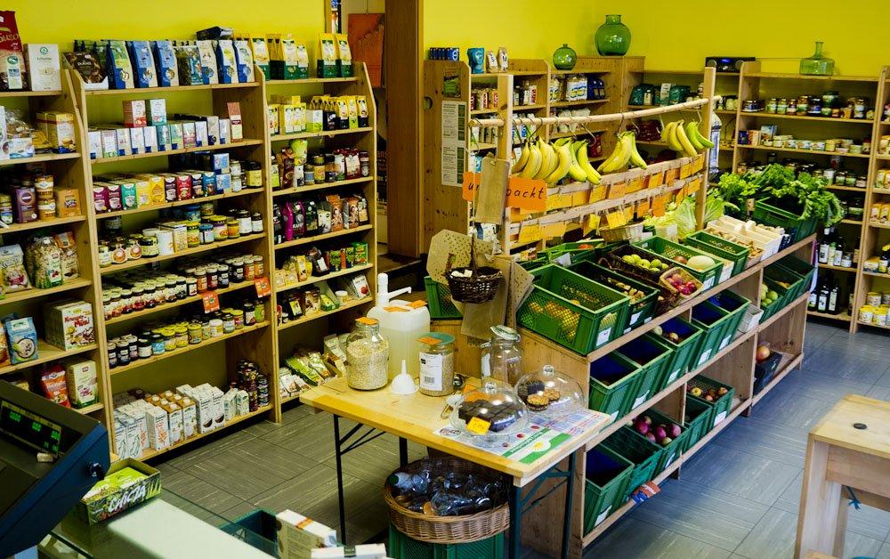 Blick in den Laden. In der Mitte sind Obst und Gemüse und drumherum sieht man Regale mit Trockenprodukten.