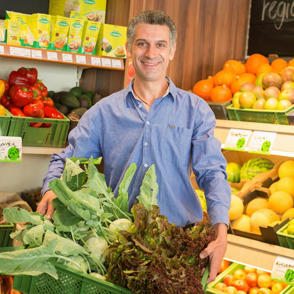 Biomarkt-Neubrandenburg – Micha Kruse mit Kiste Kohlrabi und Salat vor seinem Obst- und Gemueseregal