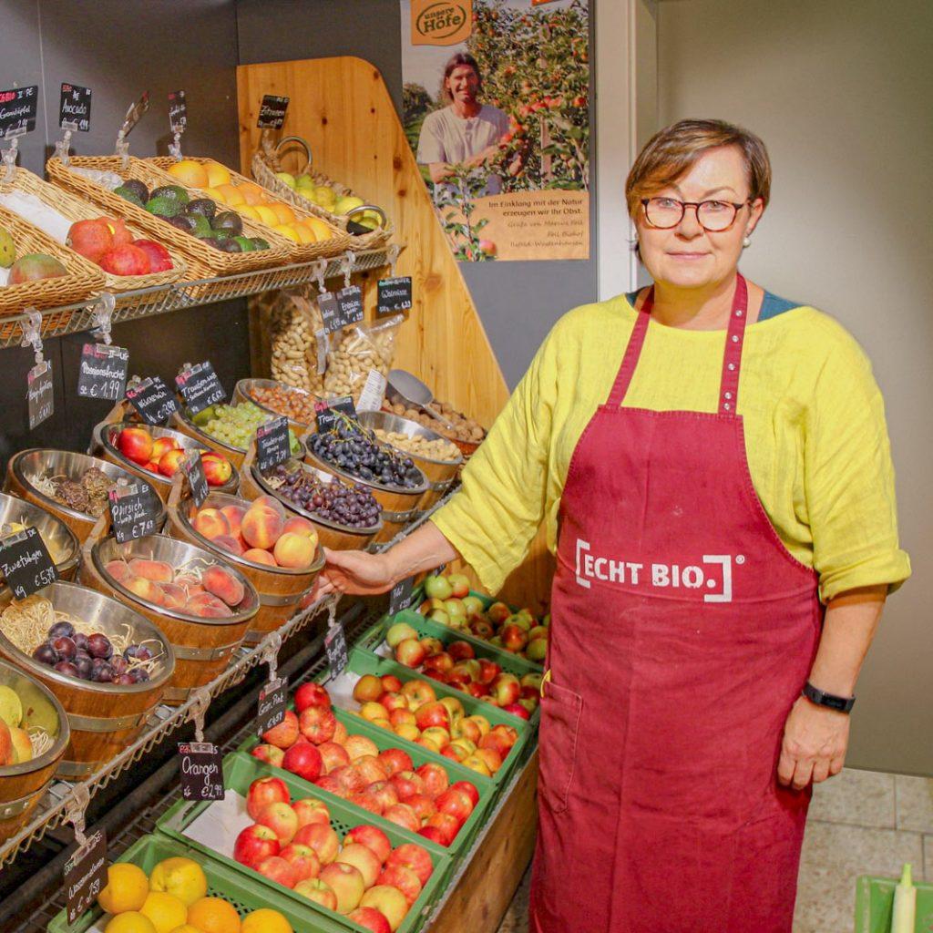 Die neue Wage - Frau Salzgeber steht neben dem Obst und Gemüse Regal