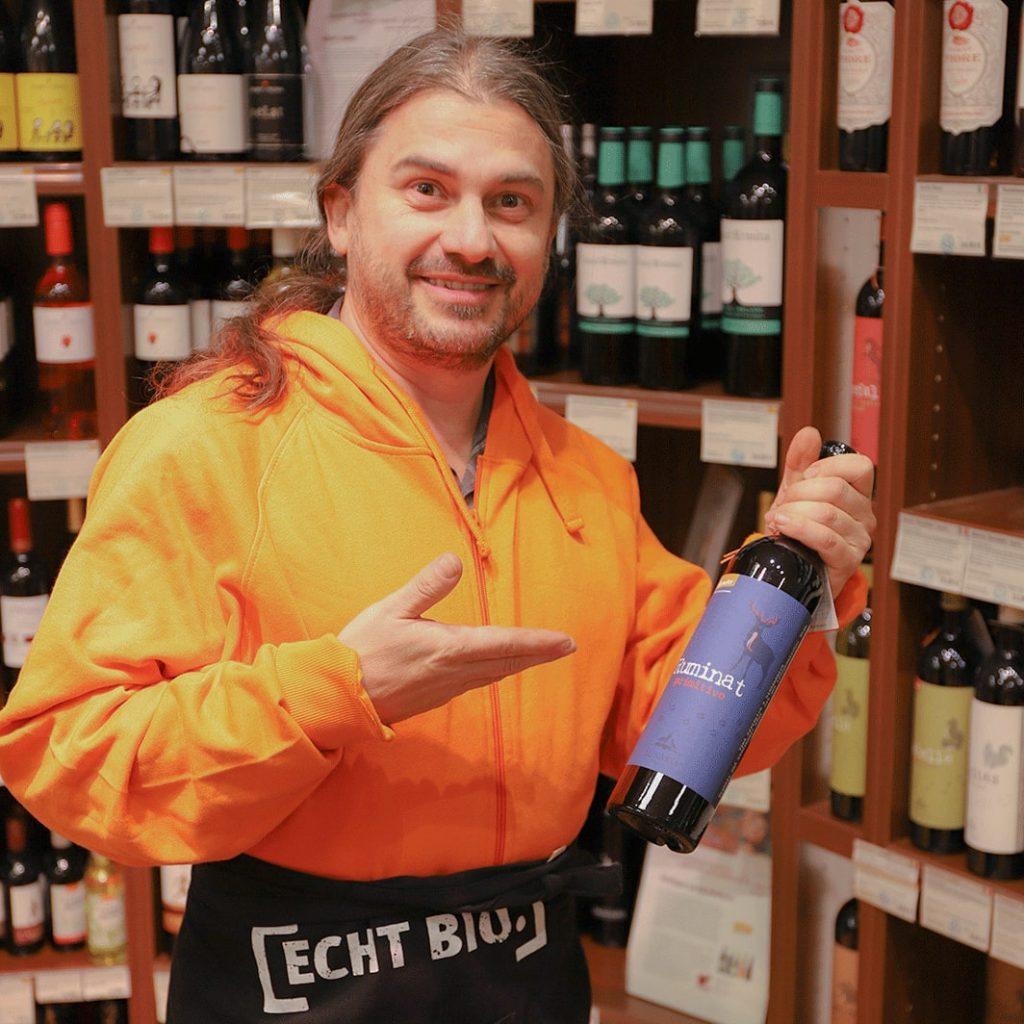 Globus-Naturkost – Thorsten Pelikan präsentiert eine Flasche Wein vor seinem Weinregal