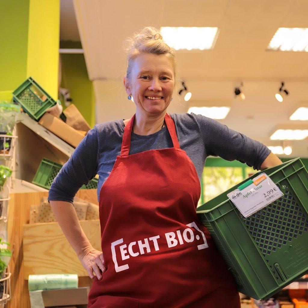 Grünschnabel - Mitarbeiterin steht im Laden und hält eine grüne Gemüsekiste unter dem linken Arm